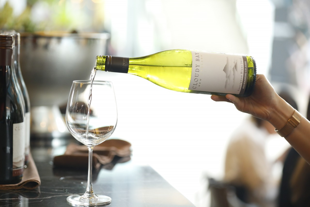 Q: Where exactly is Cloudy Bay and how does its environmental conditions  favour wine-making?